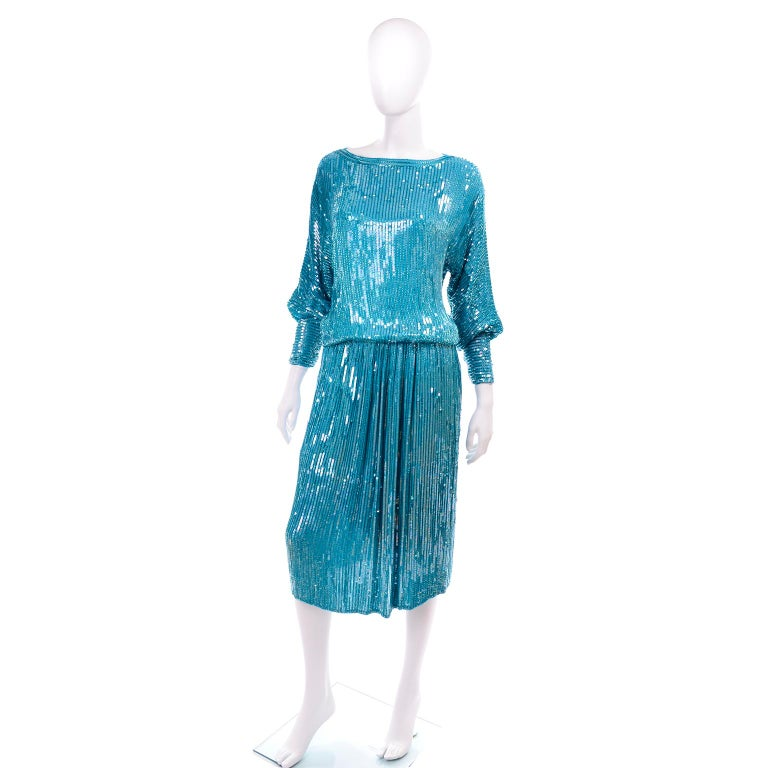 This is a beautiful vintage 1980's 2 piece dress in a gorgeous aqua silk covered with aqua beads and sequins.  This heavily beaded sequin outfit includes a sweatshirt style top with leg of mutton sleeves and a rounded boat neckline, and a midi skirt