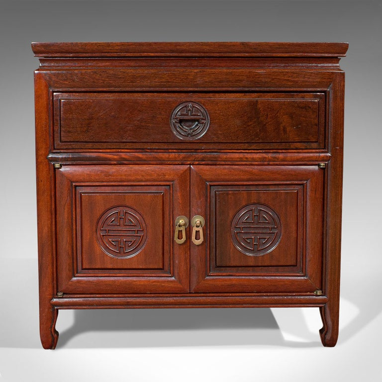 This is a vintage bedside nightstand. An Asian, teak low side cabinet, dating to the late 20th century, circa 1990.  Pleasingly square in proportion Displays a desirable aged patina Quality teak offers fine grain interest Resplendent with deep