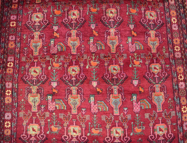 This vintage Belouch Persian carpet, circa 1940 in pure handspun and organic vegetable dyes exhibits a Nakhsh-e Samovari, or allover Samovar design, with exotic birds and floral motifs. Belouch carpets are known for their vibrant colors, as