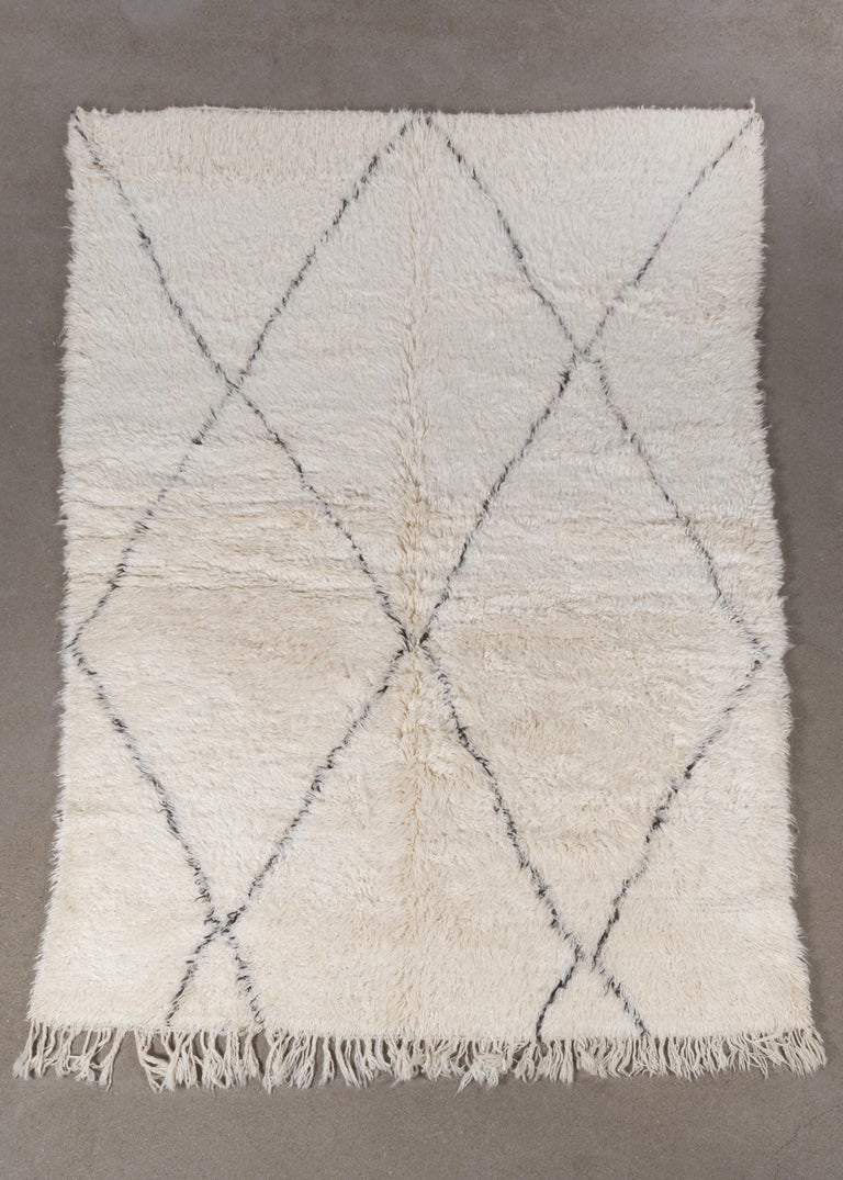This vintage Beni Ourain rug is personally selected in Morocco and has a soft ivory color due to the wool's natural color and are accompanied by dark grey stripes. The rugs are named after the Berber village 'Beni Ourain' in the mid-Atlas mountain