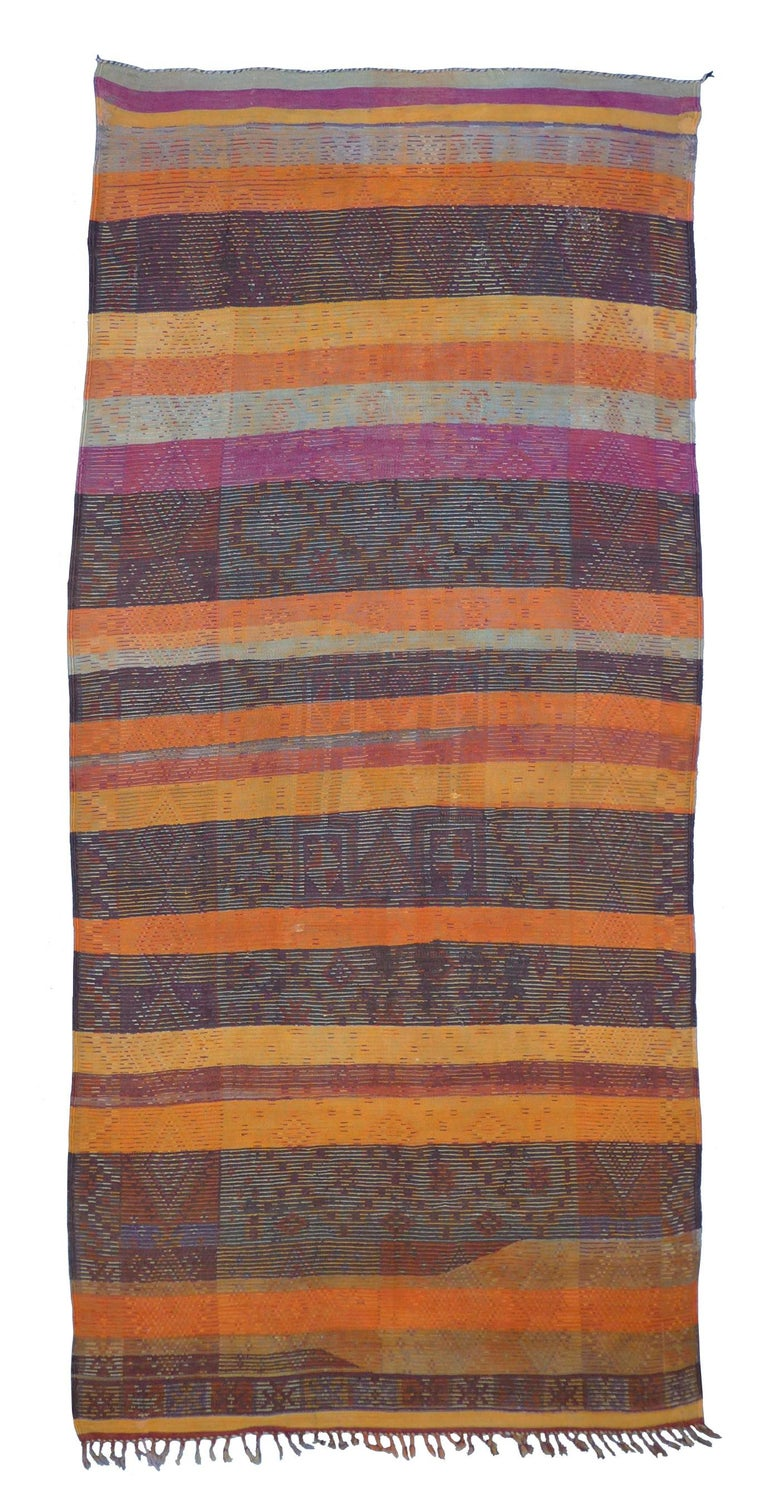 This is an exceptional vintage Znaga tribal flat-weave rug emblazoned with a field of earth tones and hand knotted motifs in brown, rust, orange, purple, olive, and red. There are a number of small repairs that match the original premium quality of