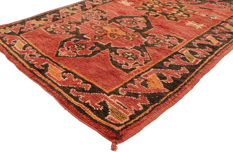 20948 vintage Berber Moroccan rug with Mid-Century Modern style. This hand knotted wool vintage Berber Moroccan rug features three floral amulets dotted with eight-point stars on an abrashed red field. It is enclosed with a botanical Meander border.