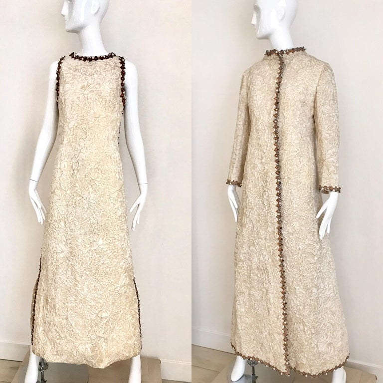 Timeless 1960s Vintage Bill Blass  for Maurice Rentner creme crushed velvet sleeveless maxi dress embellished with faux pearls and rhinestones. Dress comes with matching evening maxi coat.   Dress measurement: Bust: 36 inches/ Waist: 34 inches/ Hip: