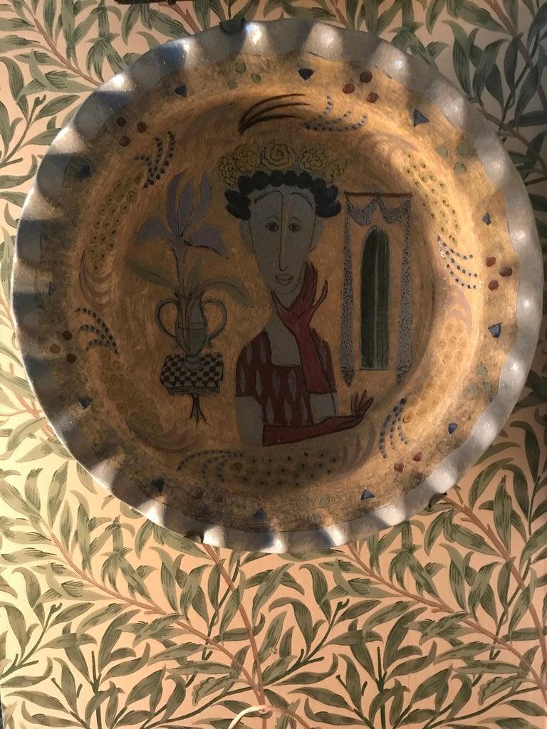Lovely vintage ceramic hanging platter with decoration on light blue fund. Signed.
