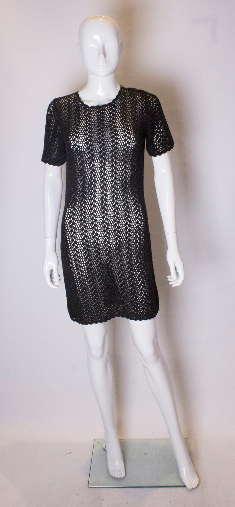 A chic crochet vintage party dress. This black mini dress has cap sleeves and a scallop edge on the hem, neckline and arms.