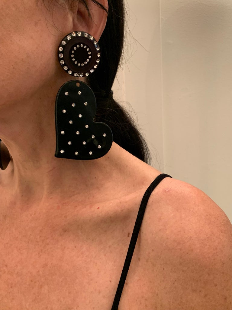 Imposing and bold over-sized black resin diamante heart shapes clip-on statement earrings. The oversized statement earrings feature two large black hearts which are adorned by clear diamante rhinestones.  The condition is excellent, lightweight and
