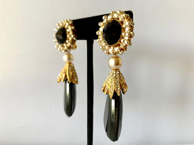 Vintage earrings by William de Lillo - comprised out of gilt metal, intricately beaded with pearls and accented by rhinestones and large faceted glass beads. Signed de Lillo, circa 1970s.