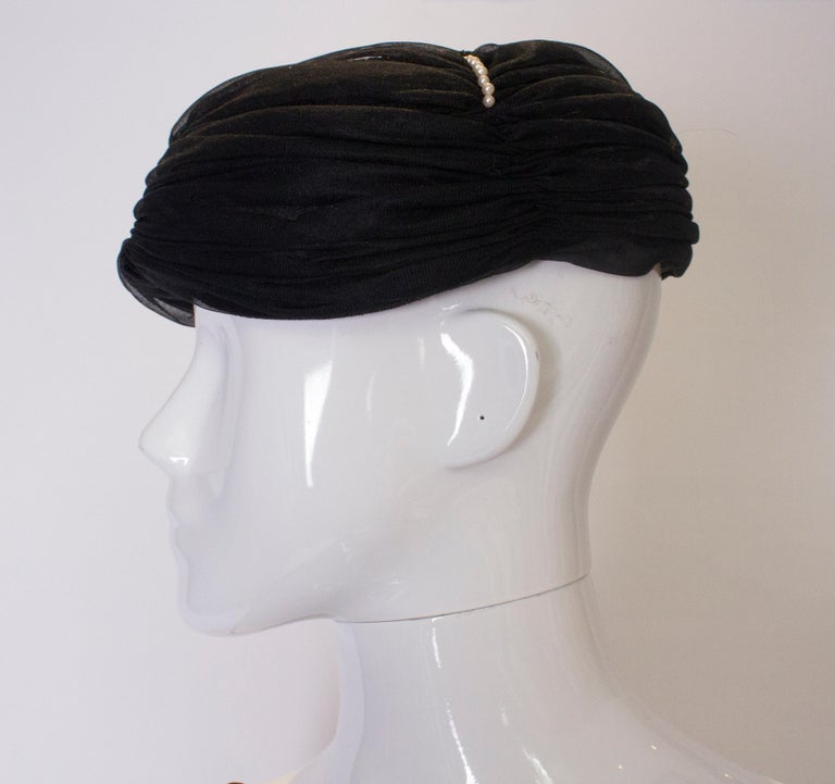 A chic black hat with gathered fabric and  four rows of pearl detail on the crown. Inner circumference 22''.