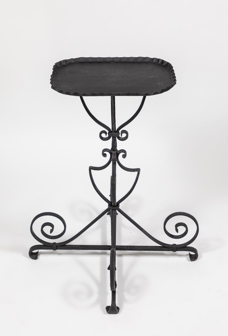 Vintage iron side table featuring a sculptural and graceful scrolled base.