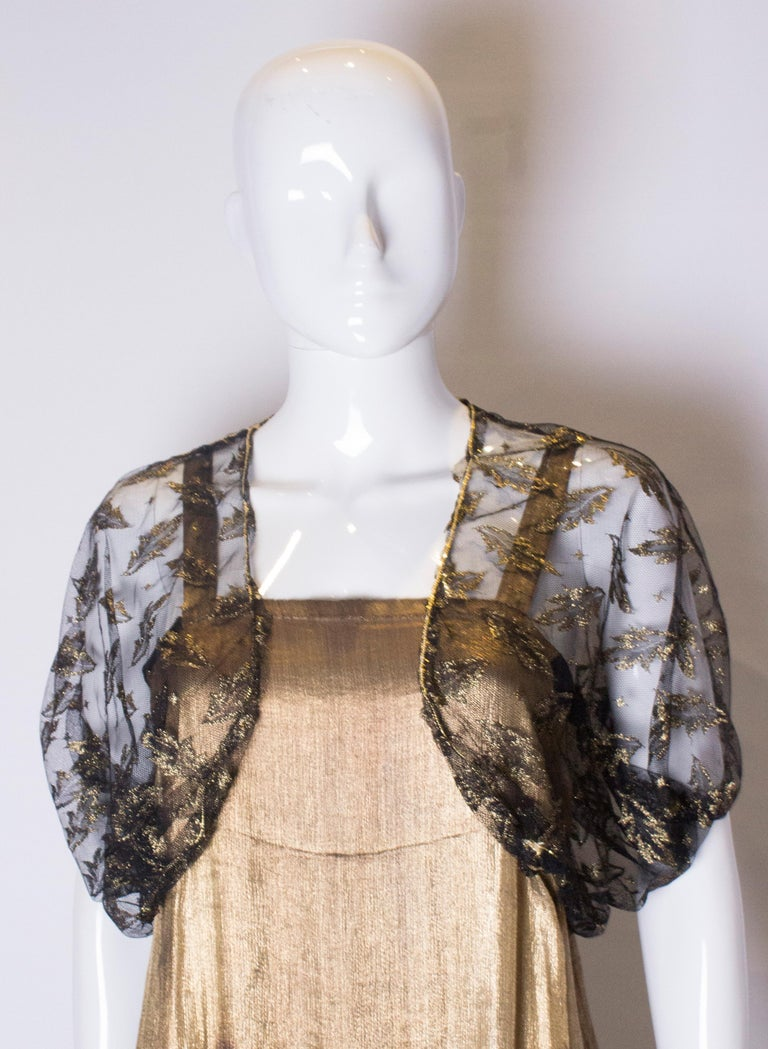 A chic black net bolero with gold leaf design. It has elastic at the hem, and a gold band on the shoulder and edge. Measurements; Bust up to 36'', length 15''