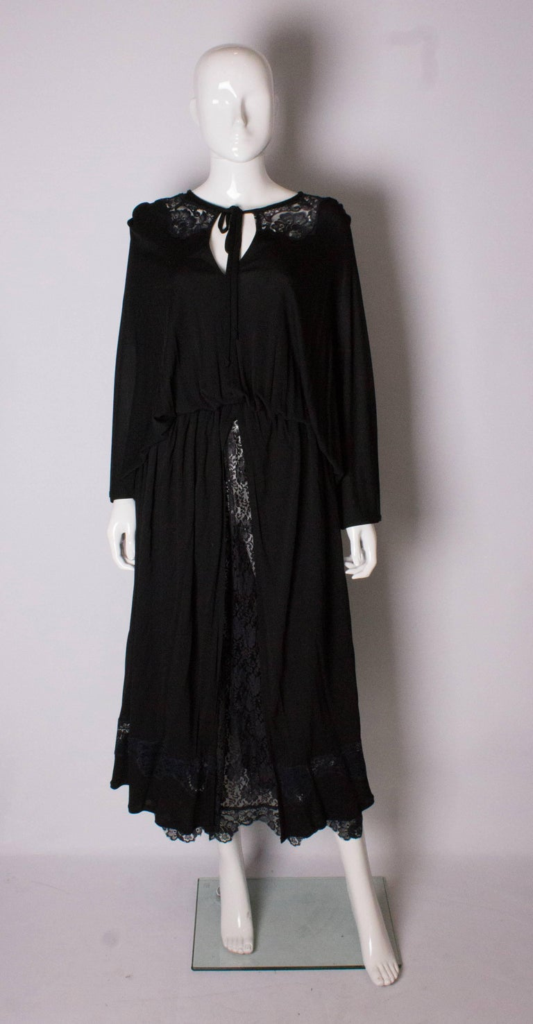 A vintage evening dress by Quorum. The black vintage dress has a lace collar and skirt , with a black split over skirt. There is a row of lace at the hem.
