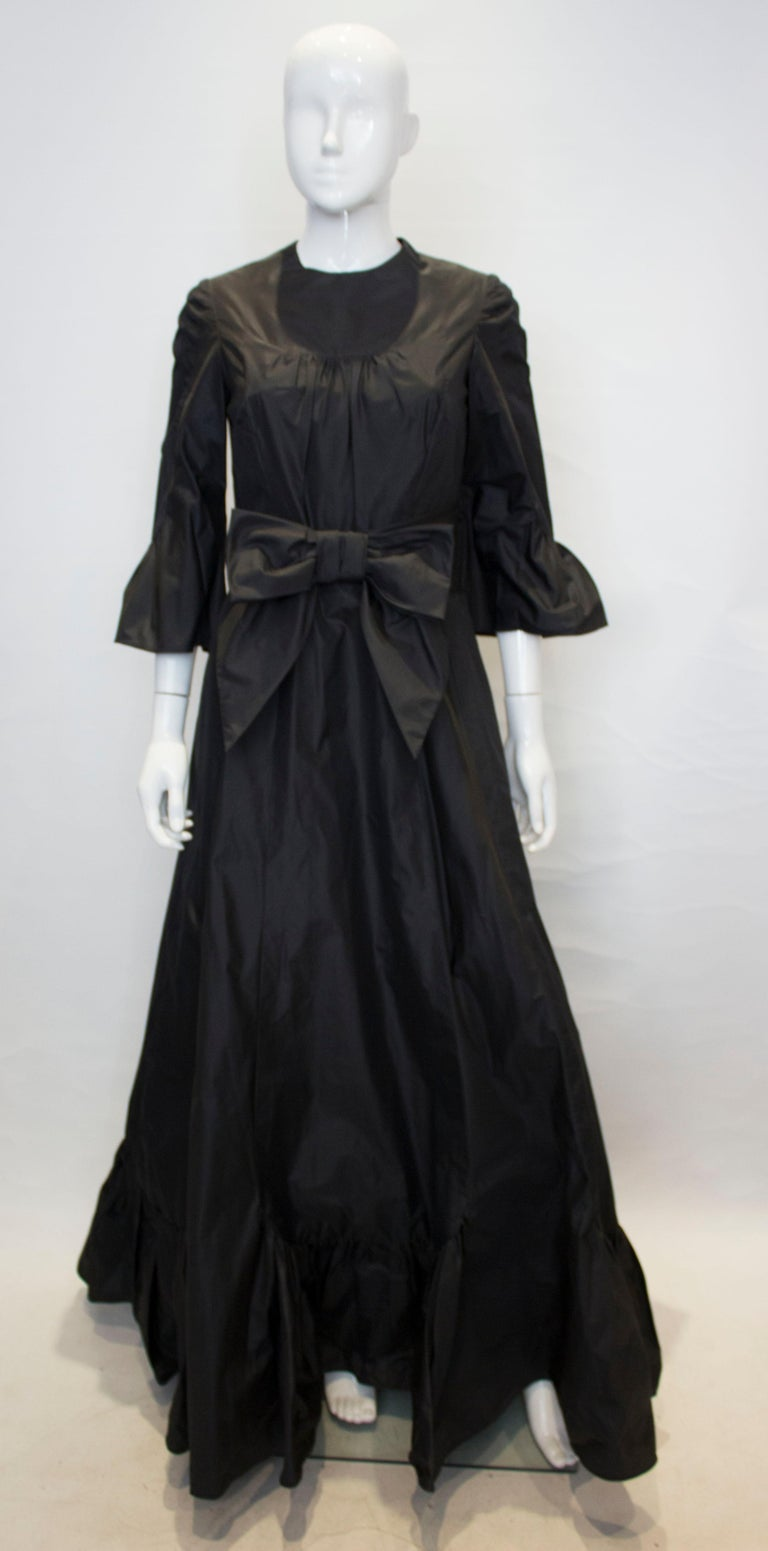 A head turning black silk taffeta gown. The dress has a round neckline, elbow length sleaves with a frill detail and a frill at the hem.  It has a central back zip and bow detail at the waist.