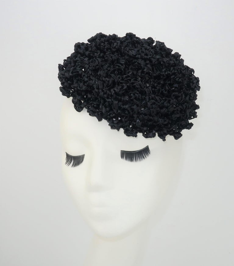 Vintage black straw curlicue fascinator style hat with two small combs stitched at the inner rim for anchoring in place.  No manufacturer's label present ... good vintage condition.  From the living estate of an amazing fashionista who was born in