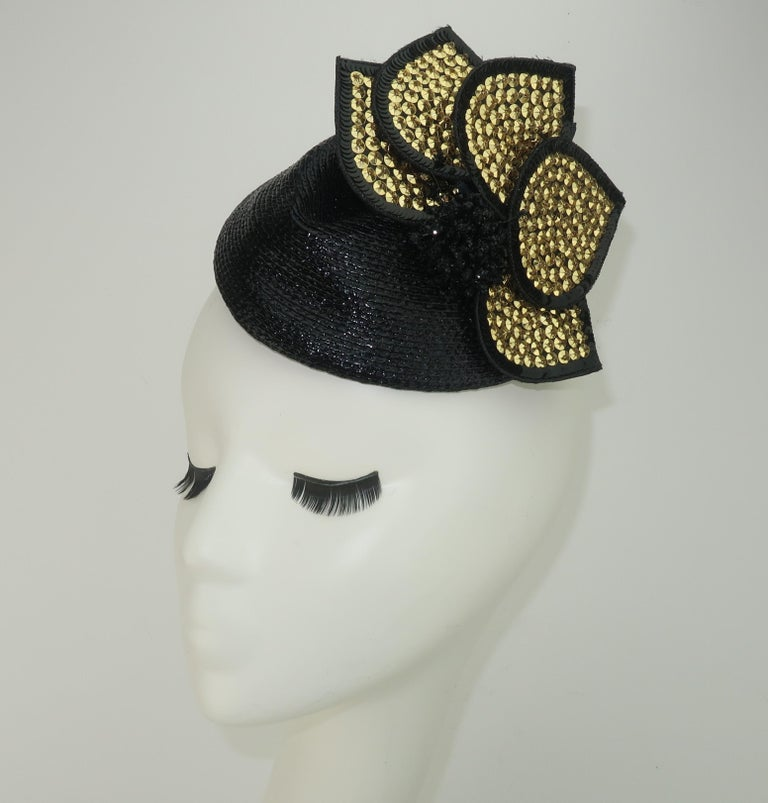 A black straw fascinator style hat with a removable gold sequin embellishment by Rosemary Peck.  Two combs are attached on the inner rim for anchoring the topper in place.  The removable embellishment could also be worn as a brooch.  From the living