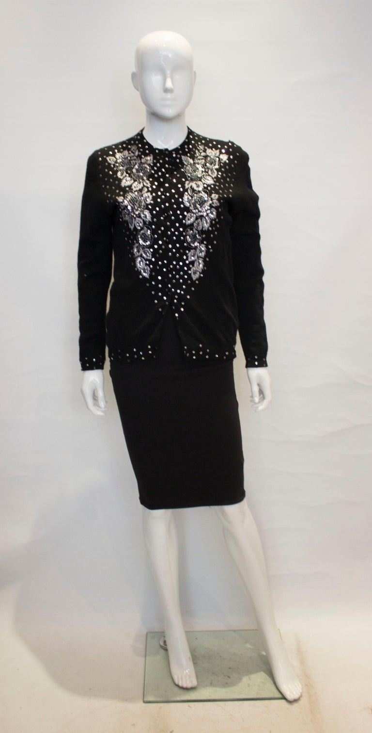 A great addition to a winter wardrobe. This black wool cardigan is fully lined, and as a wonderful beaded scallop hem. The decoration is on the front and back and it fastens with hooks and eyes.