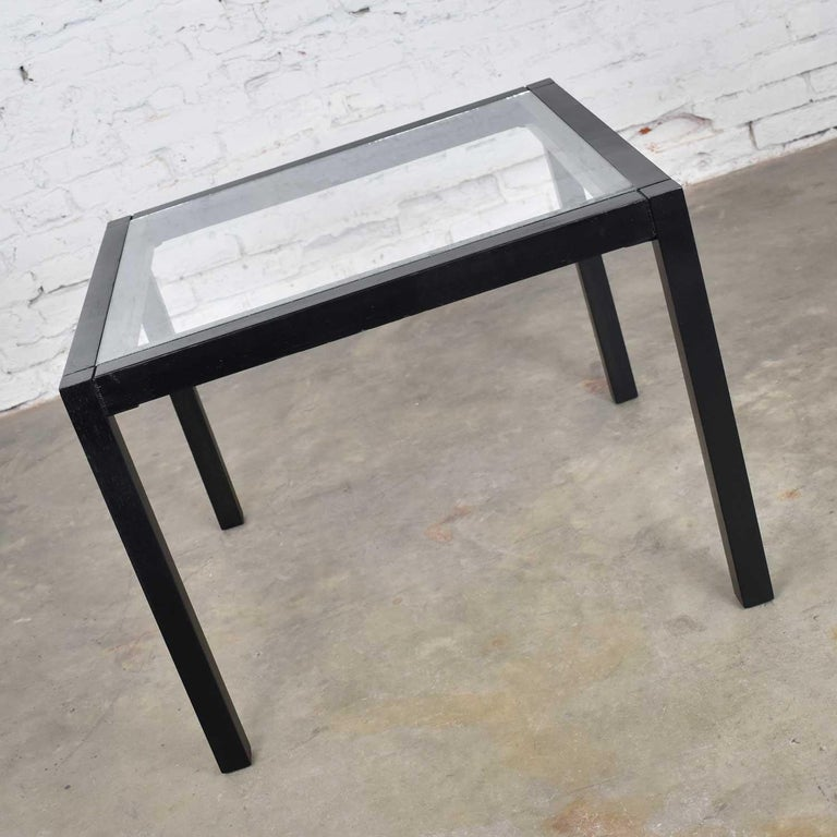 Handsome vintage blackened oak square Parsons side table with glass top. It is in beautiful vintage condition. The frame has been refinished with an oil based black leather dye and has a clear coat of polyurethane. Wood has age appropriate nicks and