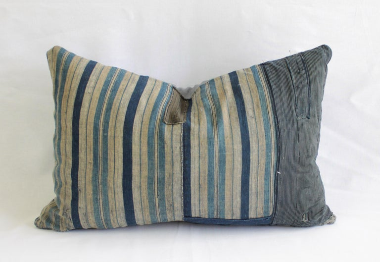 Blue patchwork vertical style pillow, with zipper closure. Back is in grey linen. Main colors are medium blue, indigo blue, light blue color, tan, with black thread running through the design. Front is lined in the same grey linen as the back, as