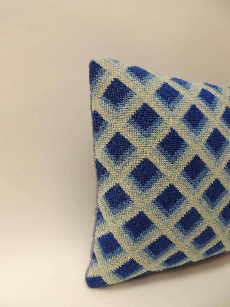 Vintage blue and white tapestry decorative bolster pillow. Textile is a modern take on traditional tapestries. Decorative bolster pillow depict a trellis design in three shades of blues, royal blue, sky blue and powder blue. Backed with homespun