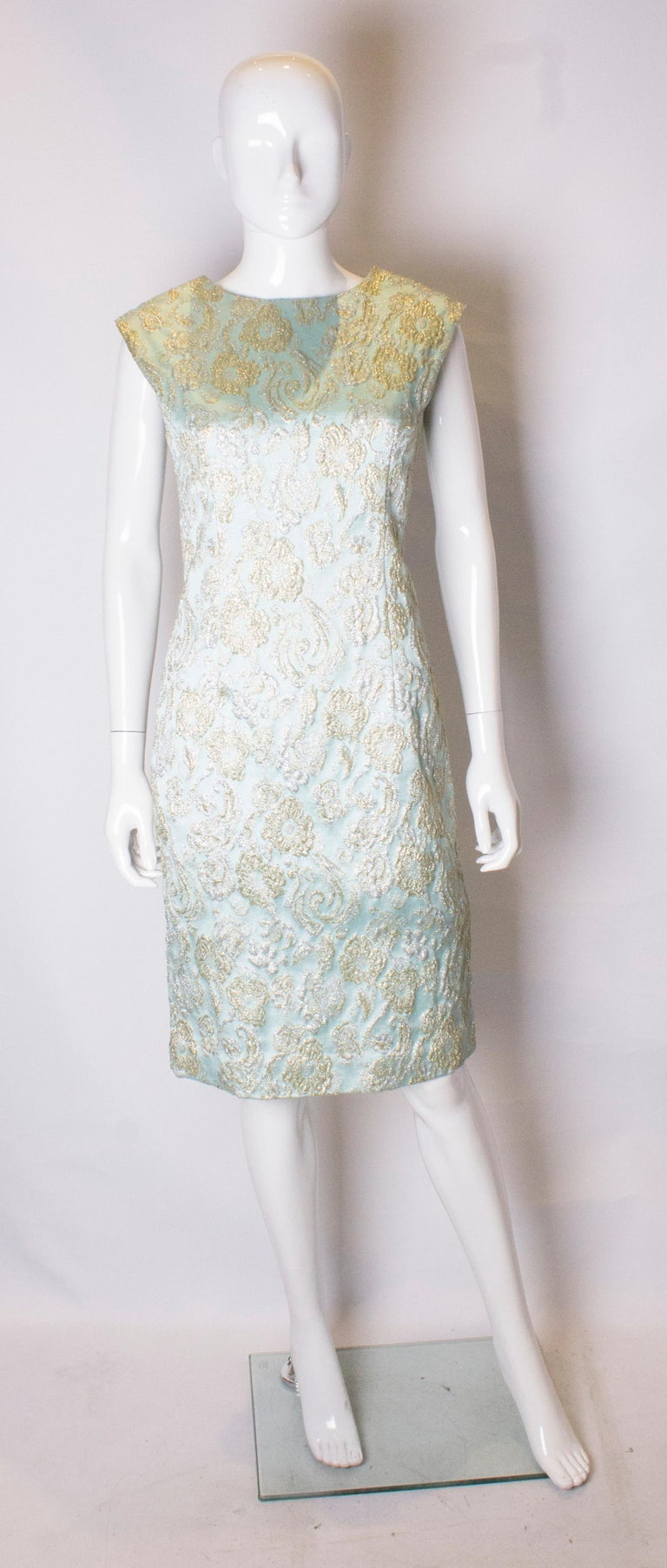 A pretty headturning cocktail dress. The dress is in a blue fabric with gold and silver embellishment. It has a  drape effect on the back and a central back zip. The dress is fully lined.