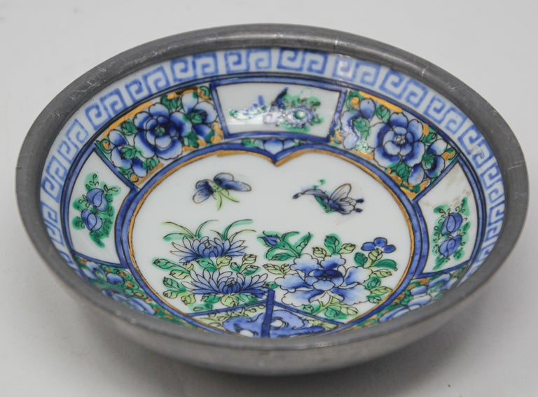 Vintage blue and white porcelain bowl catchall encased in pewter. Blue and green floral design with gold accents hand painted on a white porcelain bowl encased in pewter.  Made in Hong Kong in the 1970s.  Use as a catchall or decorative bowl.