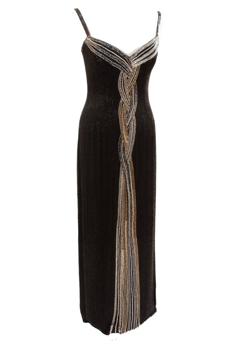 This fabulous evening gown was made by Bob Mackie in 1982, around the time he opened his ready-to-wear boutique.  Made from black silk, it's covered in tons of black jet beads and features a braid of silver and gold beads and white rhinestones at