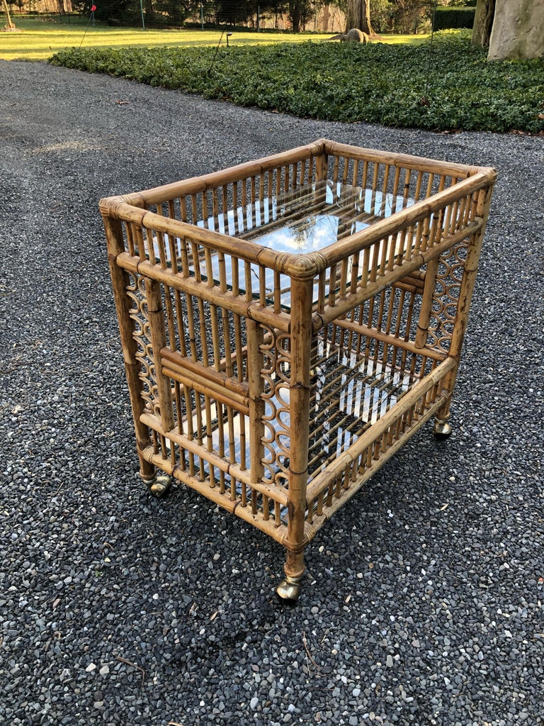 A midcentury bar cart in bamboo having two glass shelves for holding glasses, bottles and ice. The bamboo is a great color and is in excellent condition. The cart is easy to move as it is on casters.