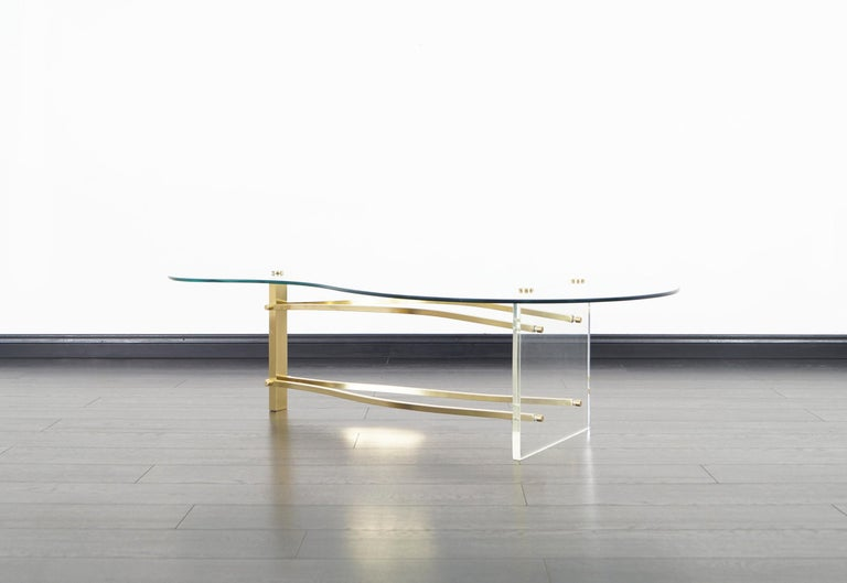 Vintage brass and Lucite coffee table in the manner of Charles Hollis Jones. Features a kidney shaped glass top that sits over a unique sculpted brass stretchers that's connecting to a square Lucite base and brass leg.