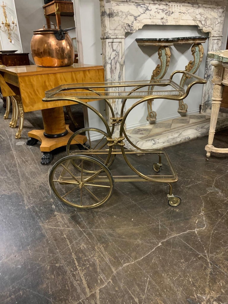 Beautiful decorative vintage brass bar cart. The piece has a glass top and another glass shelf on the bottom. A great accessory!