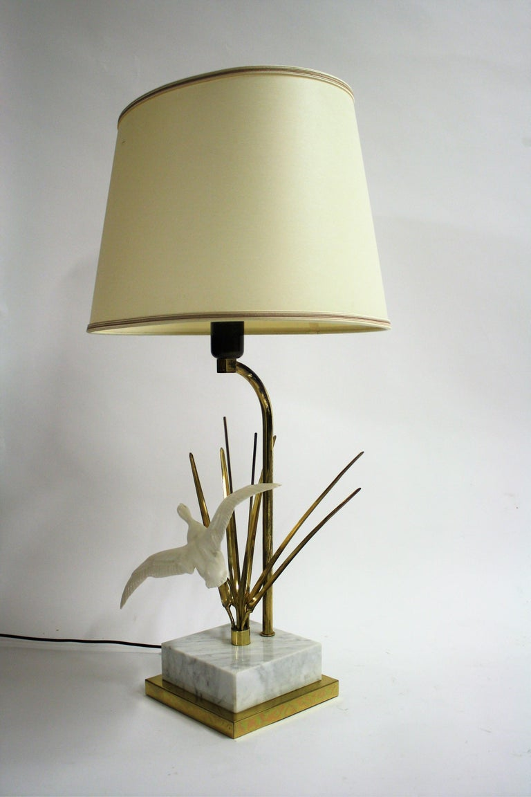 Vintage Hollywood Regency bird table lamp.  The lamp is made of brass, has a marble base and a resin bird sculpture.  Beautiful Hollywood Regency style lamp.  Comes with the original fabric shade with golden lining.  1970s -