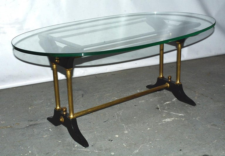 The vintage coffee table has a base made of brass fluted tubing that connects black wood feet and braces, the latter of which holds a rectangular black iron frame upon which the oval glass top rests - contemporary with classical details. Table base