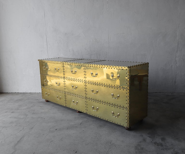 Love brass, look no further. The beautiful brass clad and riveted nine-drawer dresser by Sarreid Ltd.  Minor patina, dings, dents, and fine scratches from age and use, not perfect but overall pretty good condition, see images.