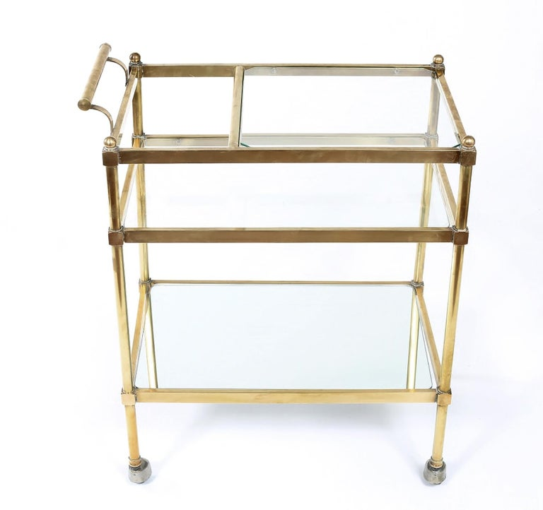 Stunning Italian three tiered brass/glass/mirror bar cart with space for bottles & side handle. The top two shelves are glass with the exception of the bottom shelve which is mirror shelve . The cart is in very good vintage condition with wear