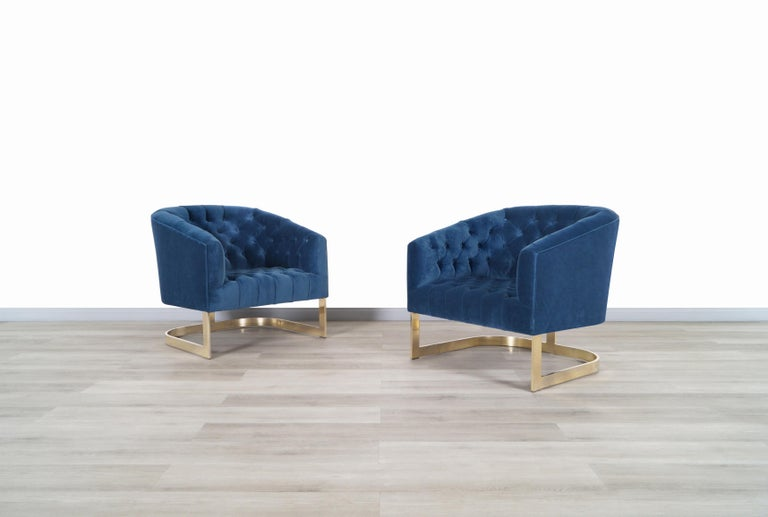 Wonderful vintage brass lounge chairs designed attributed to Milo Baughman in United States, circa 1970s. Each chair has been professionally reupholstered in a tufted design with soft midnight blue velvet. These chairs stand out for their floating
