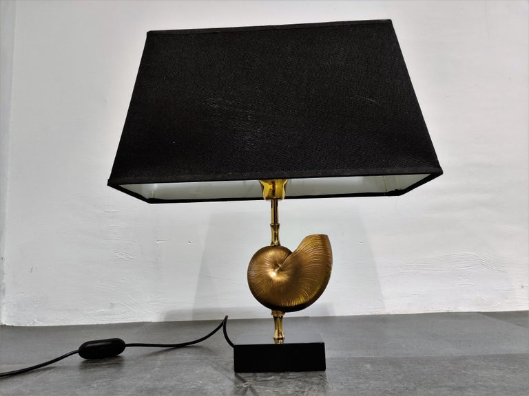 Beautiful brass nautilus shell table lamp in the style of Maison Charles.  This luxurious lamp has a golden nautilus shell center piece.  Good condition.  The lamp works with one standard E27 light bulb and is tested for safe use.  1970s,