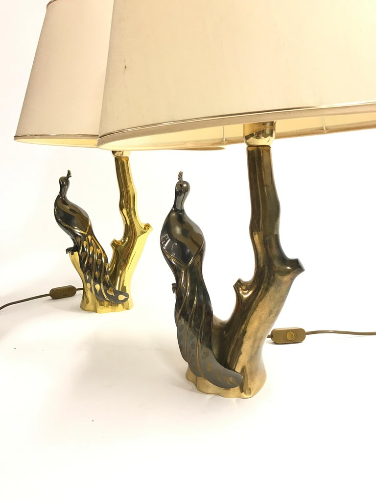 Pair of vintage brass table lamps depicting peacocks sitting on a branch.  The lamps where designed by Willy Daro.  Good condition, tested and ready for use with a regular E26/E27 light bulb.  Both lamps come with their original and good