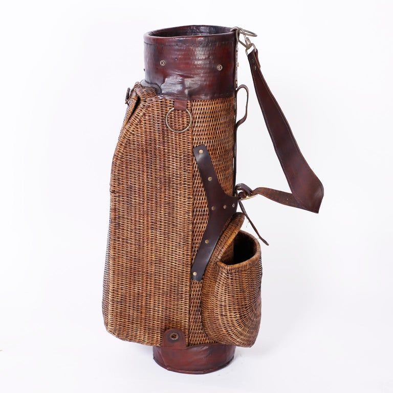 Anglo Indian British colonial style golf bag crafted with wicker over a wood frame with storage compartments and featuring brown leather straps, neck, and foot.