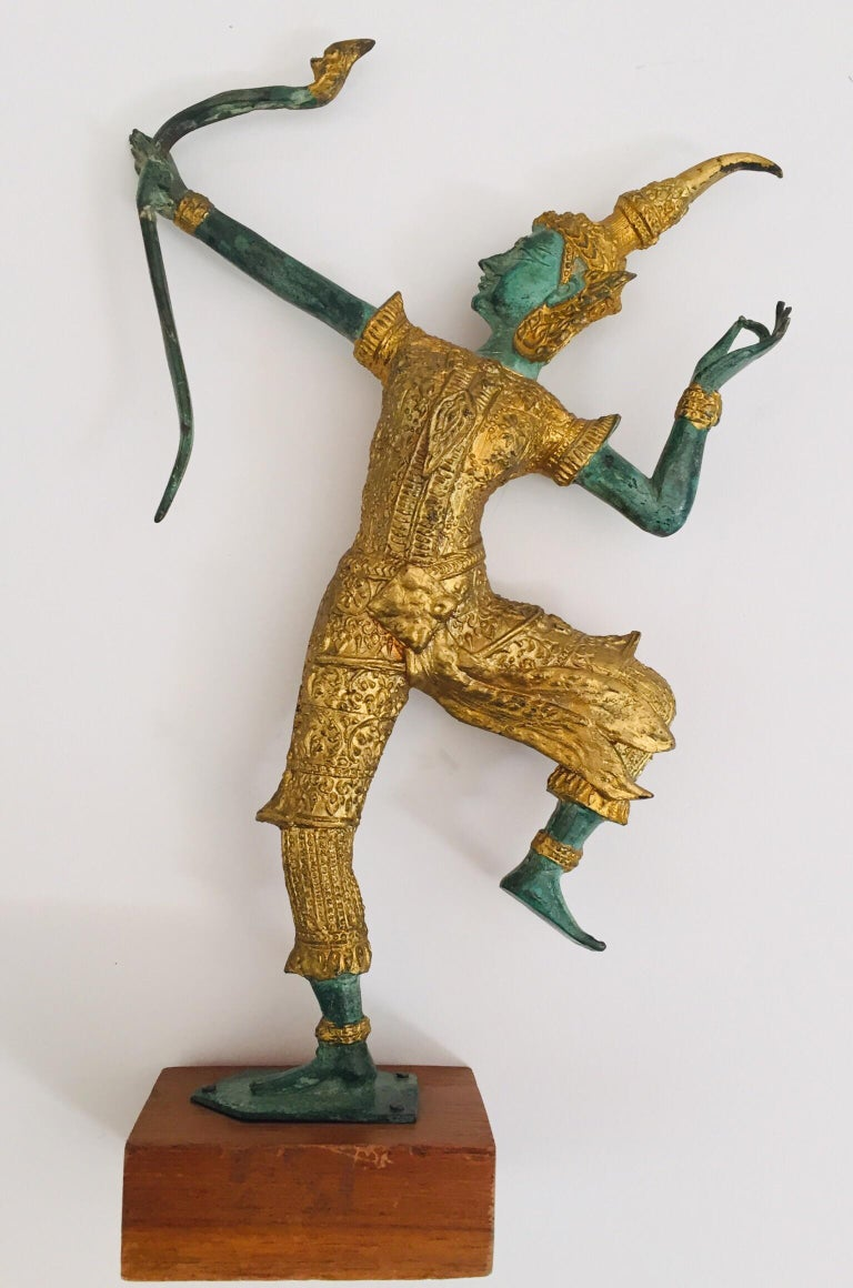 Vintage bronze statue in gold and green of Prince Rama shooting an arrow.