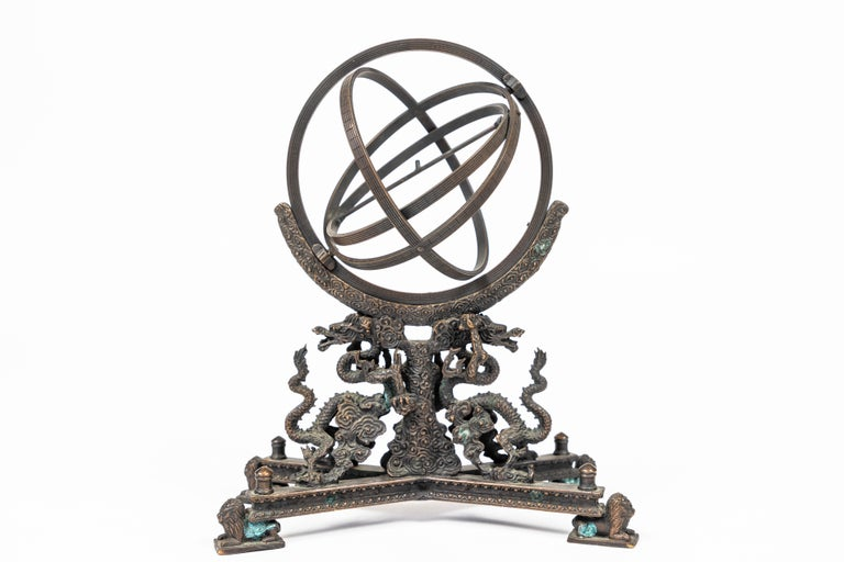 Vintage bronze rotating sphere on a base of decorative dragons and lions.