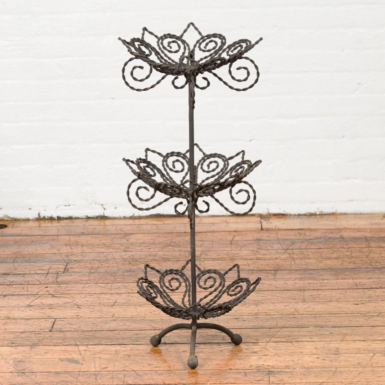 A vintage bronze three-tiered stand from the mid-20th century, with scrolled motifs. Created with the traditional technique of the lost-wax (à la cire perdue) that allows a great precision and finesse in the details, this tiered stand features three