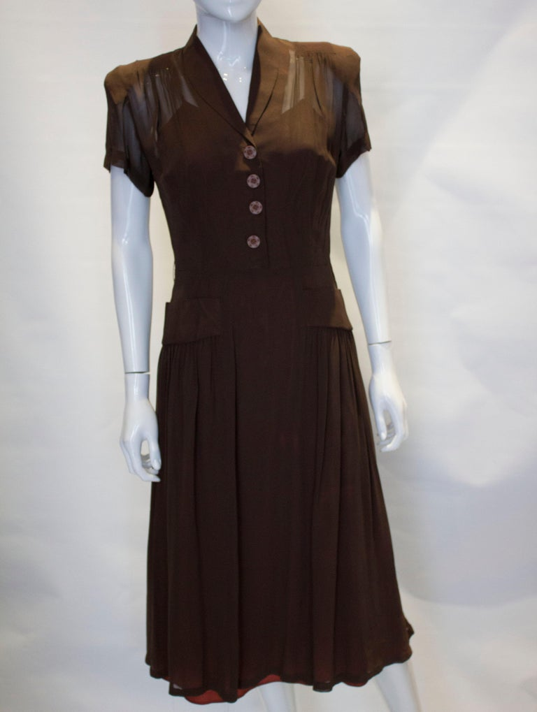 A pretty dress from the 1940s. The dress has a shawl collar, side zip opening, gathering at the shoulders and two pockets at waist level.