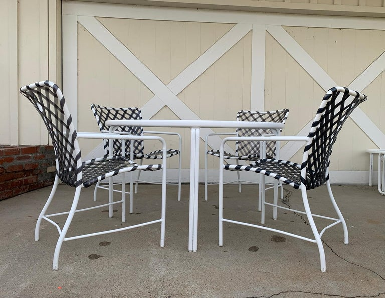 Vintage patio set comprising of 1 round table and 4 armchairs designed and manufactured by Brown Jordan from the Tamiami Collection. The set is in very good condition, with normal wear which includes nicks and scuffs on metal, the vinyl straps are