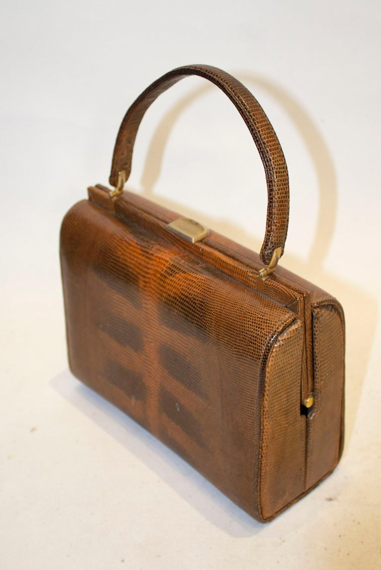 A vintage brown lizzard top handle hand bag.  The bag is lined in suede , and has one zip pocket,  one pouch pocket and a poppe pocket.  Measurements: length 9''.width 4'' height ''