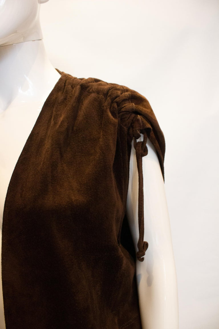 Great for Fall, a vintage brown suede waistcoat by Beged Or. The waistcoat has gathering on the shoulders, two front pockets and a tie at waist leval. Measurements Bust up to 40'', length 35''