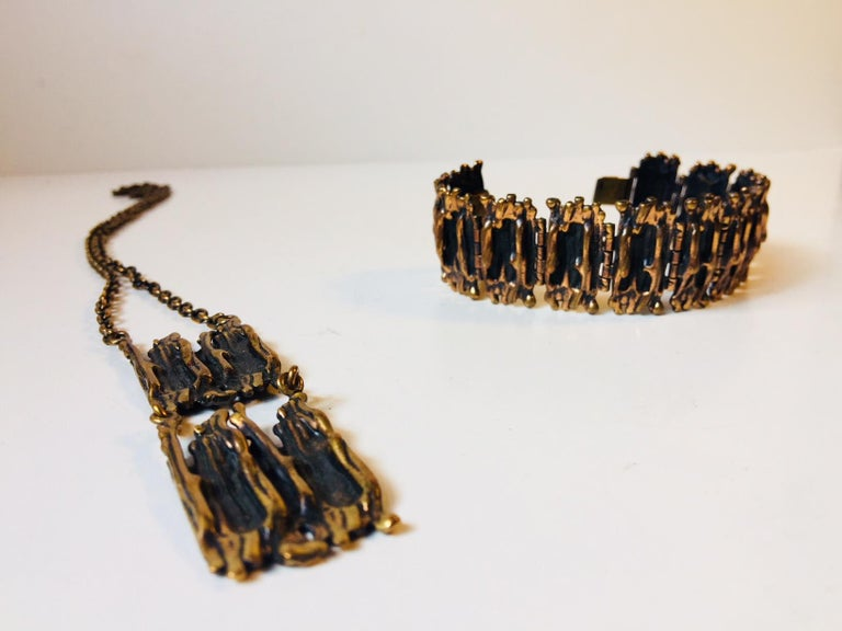 Jewelry set consisting of a necklace and a bracelet fashioned out of bronze. The style is Brutalism and the designer Pentti Sarpaneva created these pieces during the 1960s in Finland. Both pieces are signed: P. Sarpaneva. The total length of the