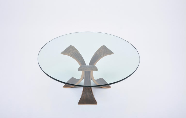 Tripod coffee table of the 1970s in the style of Mangematin. Three-legged base made of cast bronze, loose plate of 2 cm thick, slightly greenish shimmering glass.