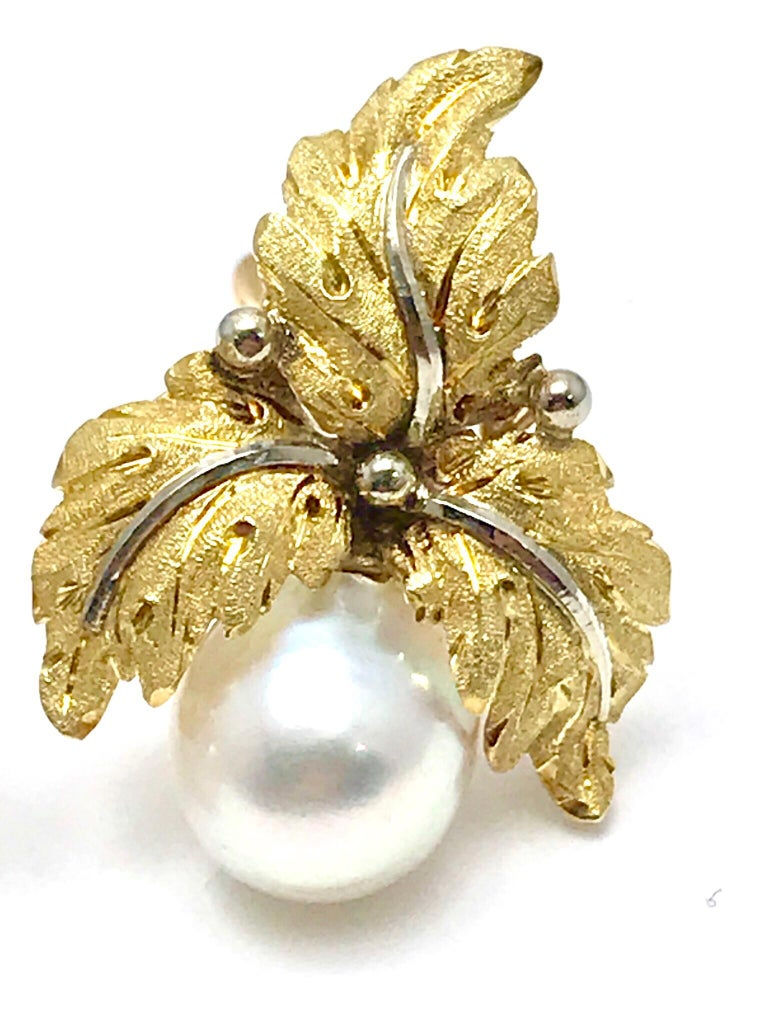 A beautiful pair of Buccellati 9.00mm Cultured Pearl and 18 karat white & yellow gold leaf clip earrings.  The leaves consist of brushed yellow gold foliage, with white gold stems, and the  pearl suspended from the three leaves.  They measure 1.00