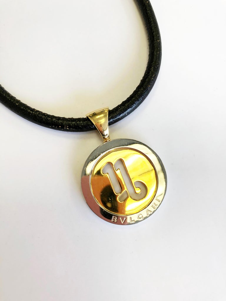 Vintage Bulgari necklace with cord and 18k yellow gold and steel pendant.  Iconic design that can be layered with other necklace or on it's own casually.