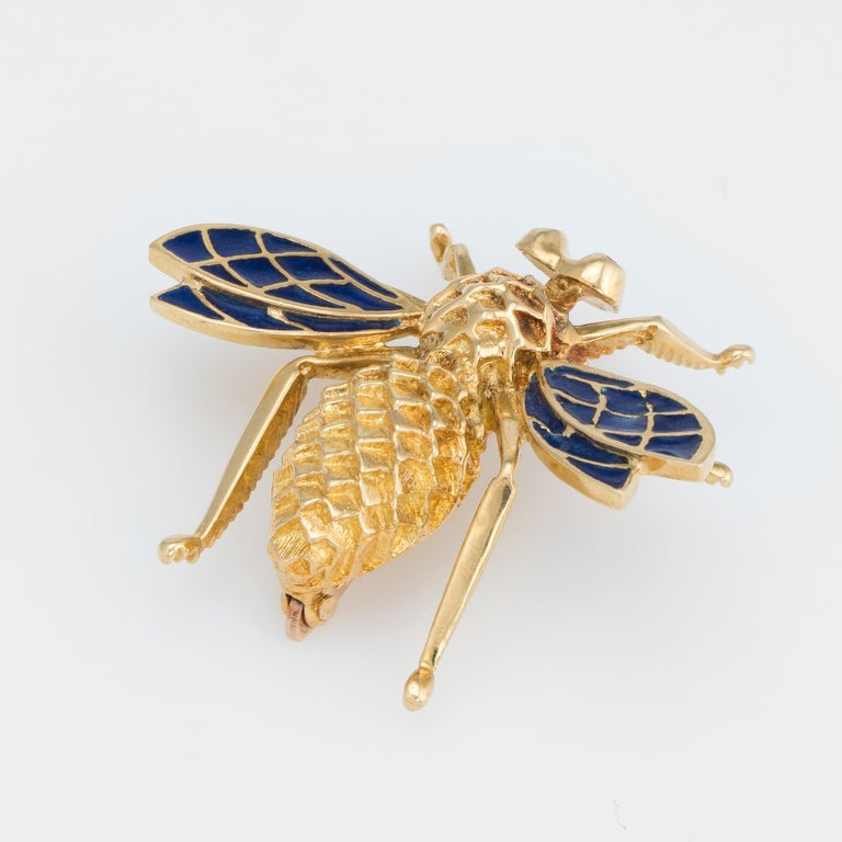 Finely detailed vintage brooch, crafted in 14 karat yellow gold.   Blue enamel is set into the bees wings adding color and contrast to the piece. The body of the bee features a graduated honeycomb like texture.    The brooch is in excellent original