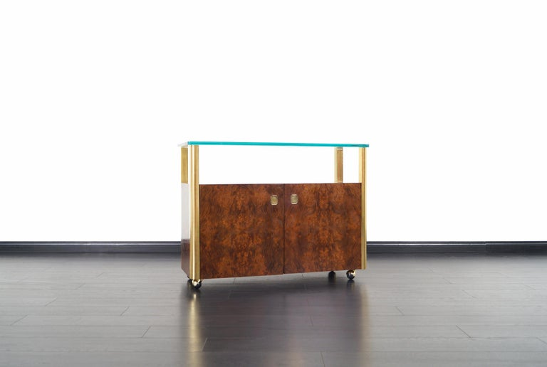 Vintage burl wood and brass bar cart designed and manufactured by Century Furniture Company in the United States, circa 1970s. This fabulous bar car features a thick glass top that sits over four brass columns, and a burl wood cabinet in the center