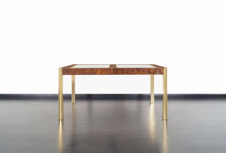An expanding vintage burl wood and brass dining table manufactured by Century Furniture Company in the United States, circa 1970s. This fabulous dining table comes with two additional 18' leaves. The table measures 96